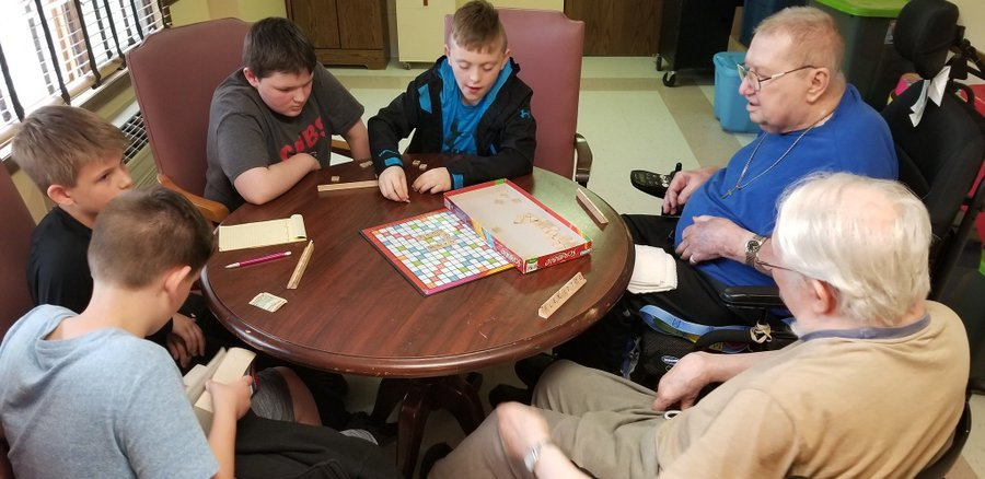 Students playing Scrabble with residents